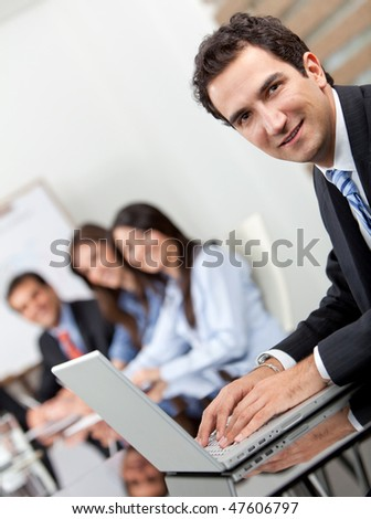 Group of business people in a office - businessman on a laptop
