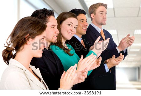 group of business people in an office applauding and smiling at success - Focus is on the girl looking at the camera - stock photo