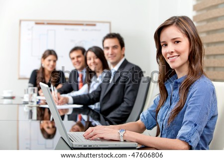 Group of business people in an office - businesswoman on a laptop
