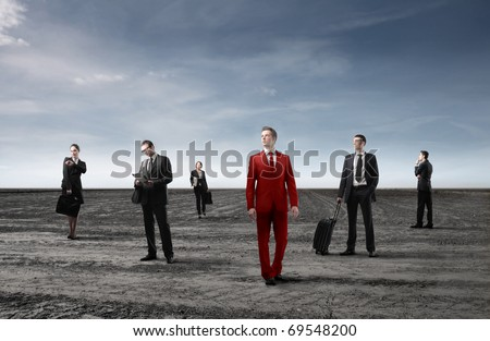 Group of business people in black and businessman in red - stock photo