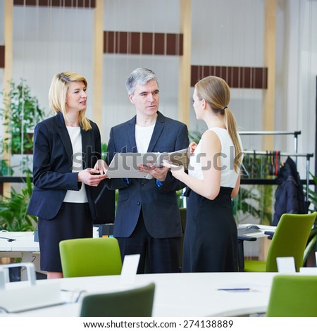 Group of business people in office talking to each other with files - stock photo