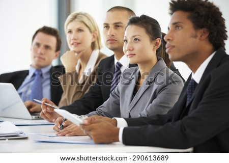 Group Of Business People Listening To Colleague Addressing Office Meeting - stock photo