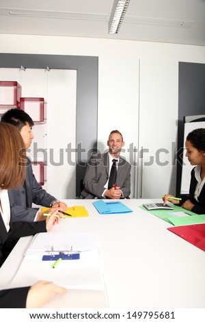 Group of business people listening to colleague addressing office meeting smiling - stock photo