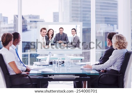 Group of business people looking at a screen against portrait of a positive team sitting at a table - stock photo