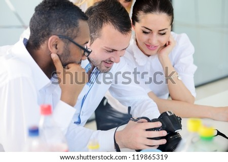 Group of business people looking at camera display - stock photo