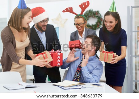 Group of business people making Christmas surprise to manager