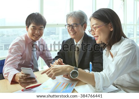 group of business people meeting with happiness emtion pointing to smart phone in hand use for modern working people lifestyle on digital technology - stock photo