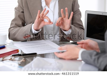 Group of business people or lawyers at meeting  discussing contract papers. Woman showing ok sign