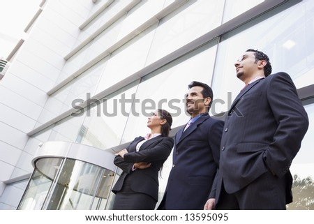 Group of business people outside modern office - stock photo