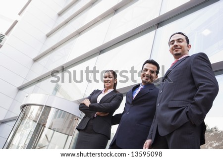 Group of business people outside modern office building - stock photo