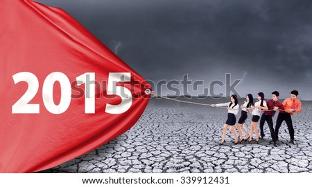 Group of business people pulling number 2015 on a big banner, symbolizing an effort for better future - stock photo