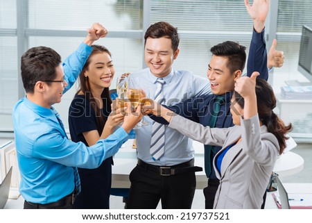 Group of business people raising thumbs-up and clinking glasses - stock photo