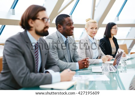 Group of business people sitting at the table during seminar