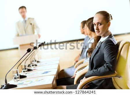 group of business people sitting at the tables at the presentation, woman looking at the camera - stock photo