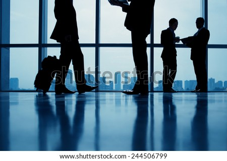 Group of business people standing against the window in the office - stock photo