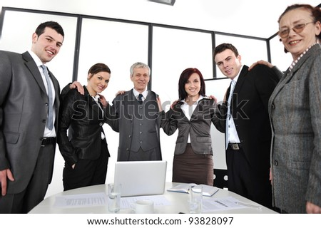 Group of business people standing at office and holding each other