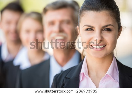 Group of business people standing in front of office and looking at camera.