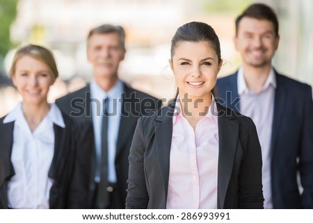 Group of business people standing in front of office and looking at camera. - stock photo