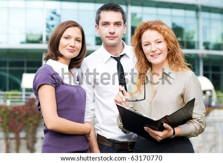 Group of business people standing in front of office building. Red-haired lady posing with documents and they all are looking at the camera.