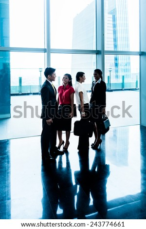 Group of business people standing in lobby or hall, a city skyline in the background - stock photo