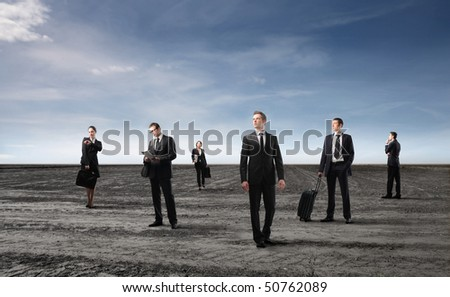Group of business people standing on a field - stock photo