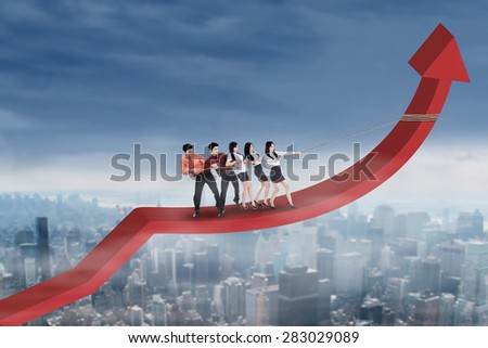 Group of business people standing on arrow and pulling it upward by using a rope - stock photo