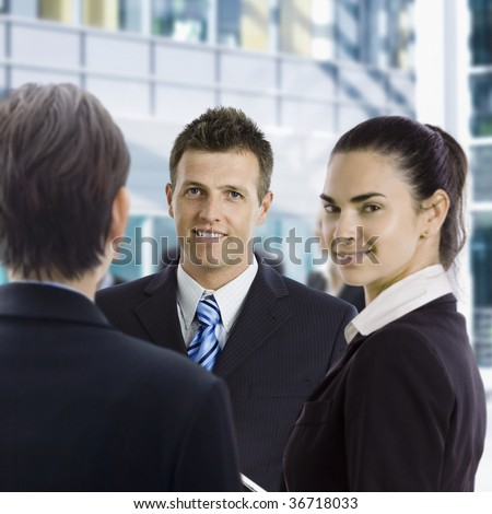 Group of business people staning on office hallway, looking at camera smiling.