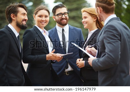 Group of business people talking at meeting outside, pretty female looking at camera - stock photo
