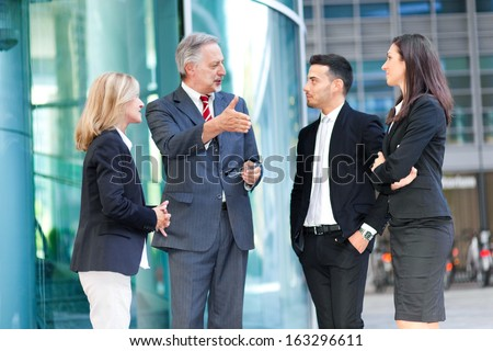 Group of business people talking outdoor in an urban setting  - stock photo