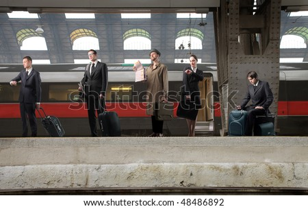 Group of business people waiting for a train on a platform - stock photo