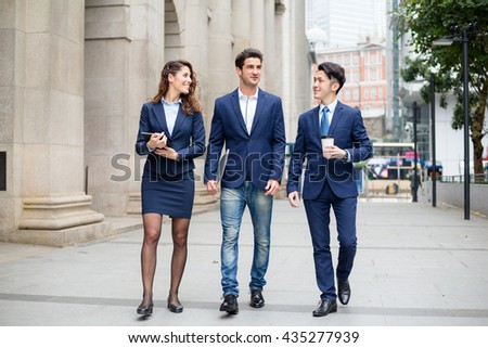 Group of business people walking at street - stock photo