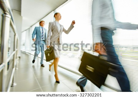 Group of business people walking down office center along window