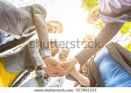 Group of business people with hands on stack. They all are young, smiling and wearing smart casual clothes. Mixed race group. Focus on the hands. Teamwork and business concepts.