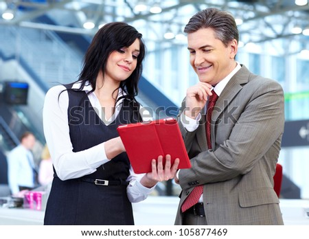 Group of business people with tablet computer in the modern urban hall. - stock photo