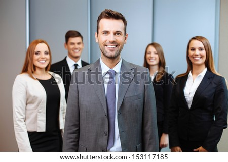 Group of business people with team leader in foreground - stock photo