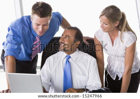 Group of business people working in office looking at laptop - stock photo