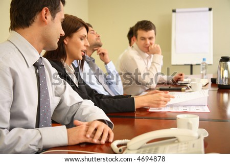 Group of business people working together at the informal meeting, focus on man in foreground. - stock photo