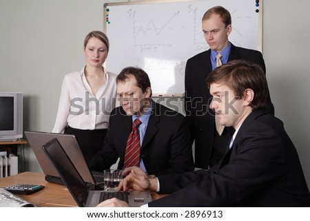 Group of 4 business people working together in the office.