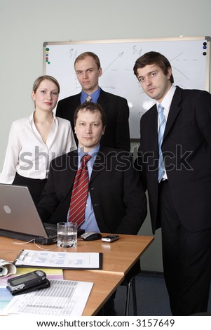 Group of 4 business people working together in the office. - stock photo