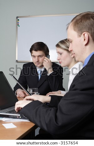 Group of 3 business people working together in the office. - stock photo