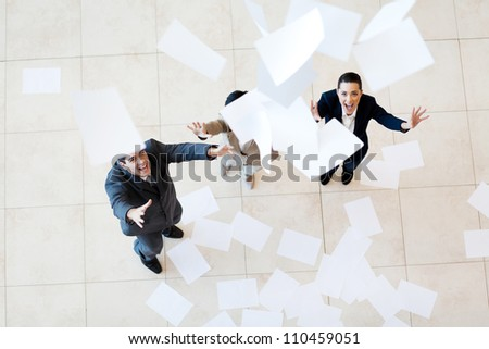 group of businessman and businesswoman catching papers falling from above - stock photo