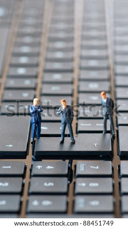 Group of businessman figurines placed on computer keyboard - stock photo