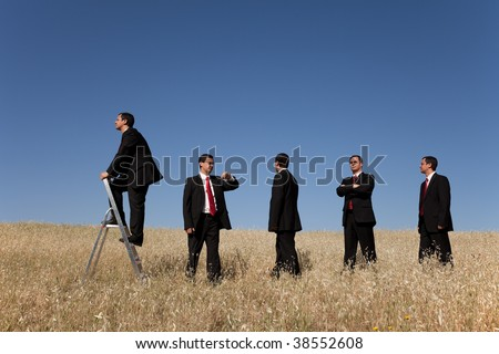 group of businessman in line waiting for there time to climb the step stairs