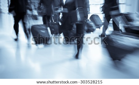 Group of businessmen carrying luggage in the airport, strong motion blur, blue tone - stock photo