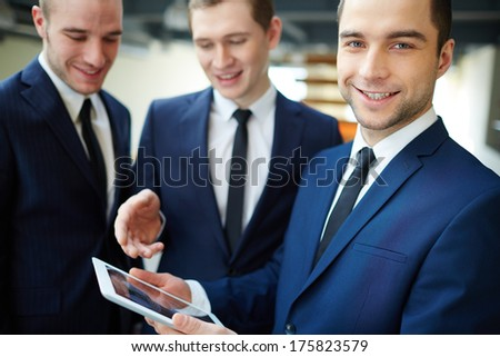 Group of businessmen discussing document in touchpad at meeting, one of them looking at camera - stock photo