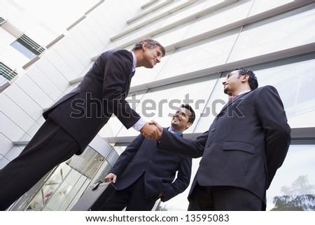 Group of businessmen shaking hands outside modern office - stock photo
