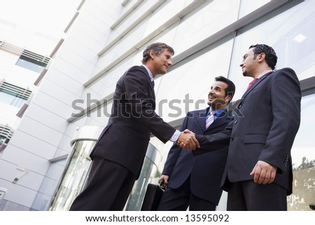 Group of businessmen shaking hands outside office building - stock photo