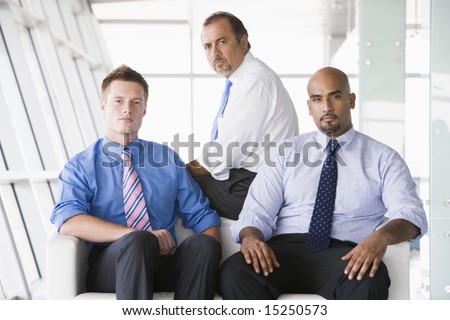 Group of businessmen sitting in office lobby - stock photo