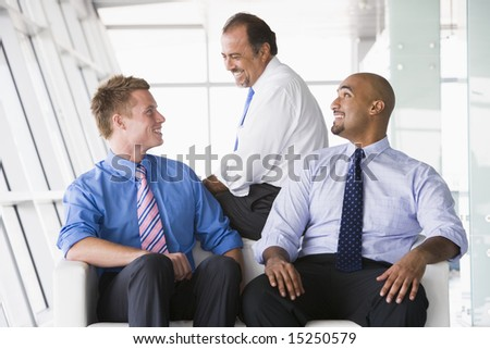 Group of businessmen talking on office lobby - stock photo