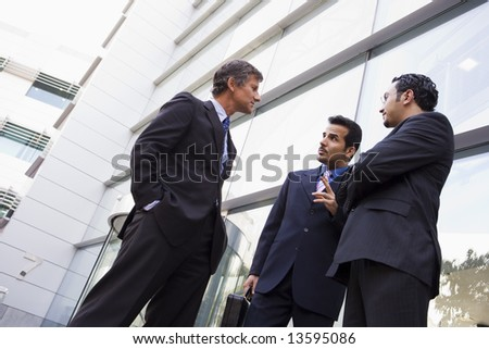 Group of businessmen talking outside modern office building - stock photo